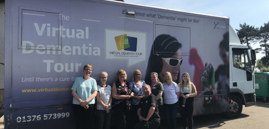 staff outside the virtual dementia tour bus