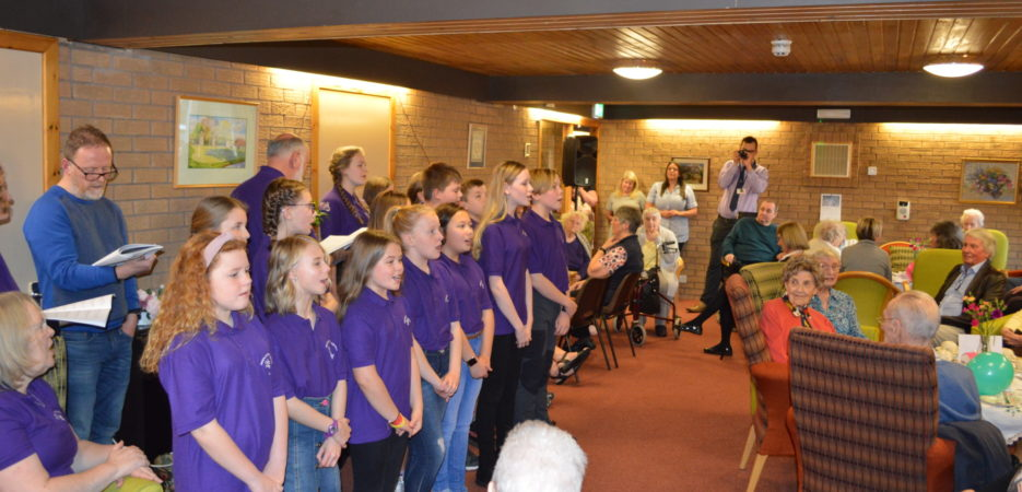 Young operatic choir singing to residents
